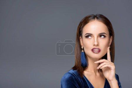 Photo pour Songeuse jeune femme avec maquillage élégant vous cherchez loin isolé sur fond gris - image libre de droit