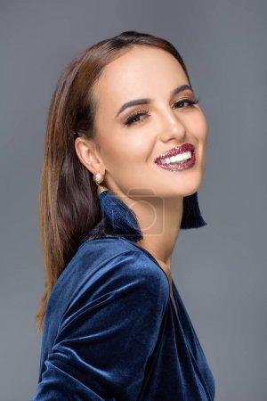 Photo pour Magnifique jeune femme en robe de soirée et élégant maquillage souriant à la caméra isolé sur gris - image libre de droit