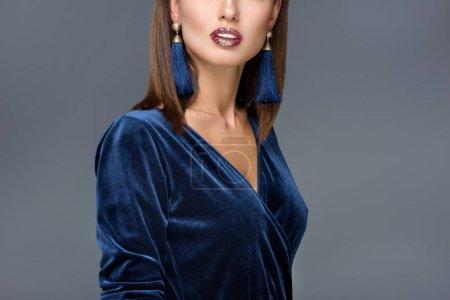 Photo pour Recadrée coup de femme magnifique en robe de soirée et les boucles d'oreilles posant isolés sur gris - image libre de droit