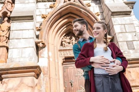 Photo pour Faible angle de vue de sourire homme étreignant femme enceinte sur la rue - image libre de droit