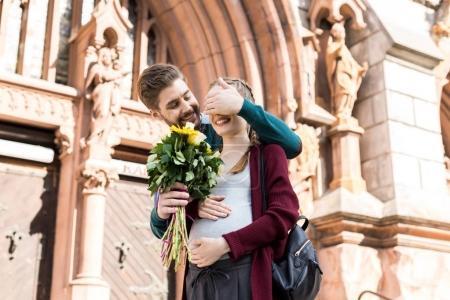 Photo pour Portrait d'homme souriant femme surprenante avec bouquet de fleurs dans la rue - image libre de droit