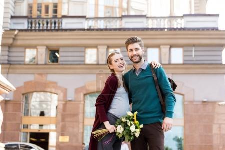 Photo pour Portrait de mari heureux et femme enceinte avec bouquet de fleurs regardant la caméra sur la rue - image libre de droit