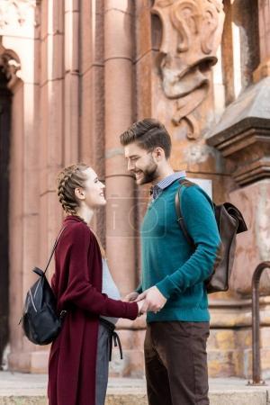 Photo pour Vue latérale du mari souriant et de la femme enceinte se regardant dans la rue - image libre de droit