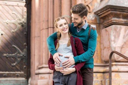 Photo pour Jeune homme toucher le ventre de la femme enceinte tout en se tenant dans la rue ensemble - image libre de droit