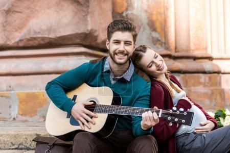 Photo pour Jeune homme jouant de la guitare pour femme enceinte tout en se reposant sur la rue ensemble - image libre de droit