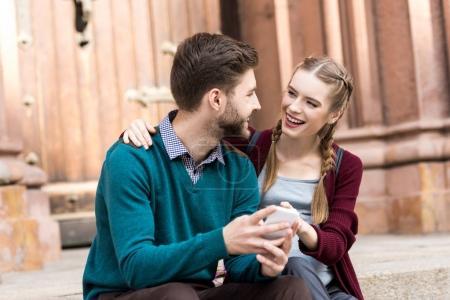 Photo pour Portrait de heureuse femme enceinte étreignant mari avec smartphone dans les mains - image libre de droit