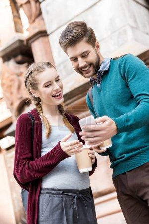 Photo pour Portrait d'homme souriant et femme enceinte avec café pour aller à l'aide d'un smartphone dans la rue - image libre de droit