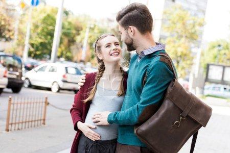 Photo pour Portrait de mari souriant et femme enceinte embrassant et se regardant dans la rue - image libre de droit