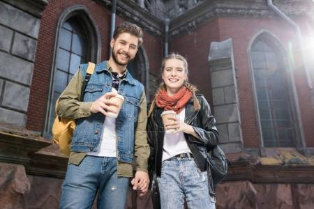 couple with coffee to go on street