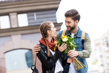 man presenting bouquet of flowers to girlfriend