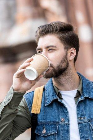 man drinking coffee on street