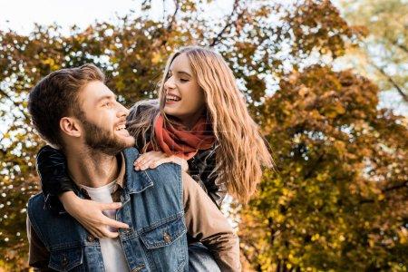 Photo pour Portrait d'un couple heureux en amour le ferroutage en automne parc - image libre de droit