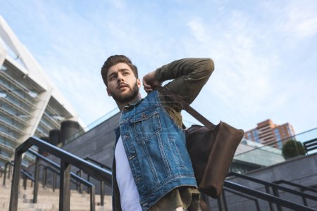 Photo pour Vue faible angle de songeur homme élégant avec sac à dos vous cherchez loin sur la rue - image libre de droit