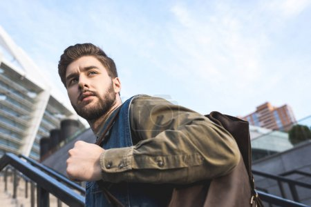 stylish man with backpack on street