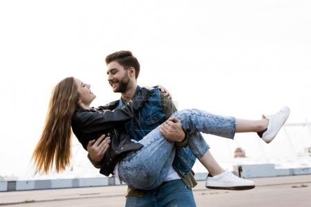 man holding girlfriend on hands