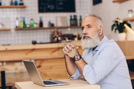 senior man with laptop in cafe