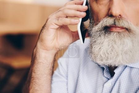 Photo pour Recadrée tir de senior homme parler sur smartphone dans café - image libre de droit