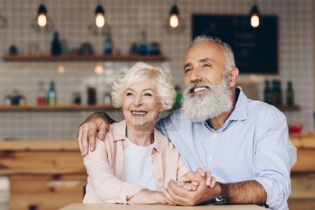 Photo pour Foyer sélectif de joyeux couple âgé regardant loin tout en étant assis à la table dans le café - image libre de droit