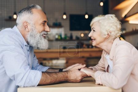 Photo for Side view of smiling senior couple looking at each other and holding hands while sitting at table in cafe - Royalty Free Image