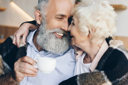 Photo for Portrait of elderly man with cup of coffee in hand looking at smiling wife - Royalty Free Image