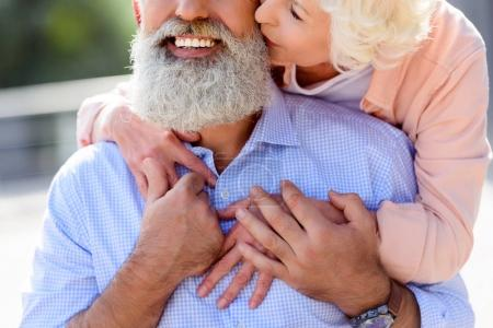 Senior woman kissing husband