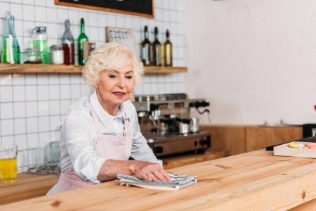 Photo for Portrait of senior worker in apron cleaning wooden counter in cafe - Royalty Free Image