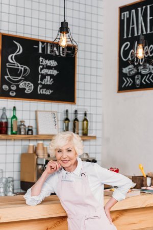 smiling senior worker at counter