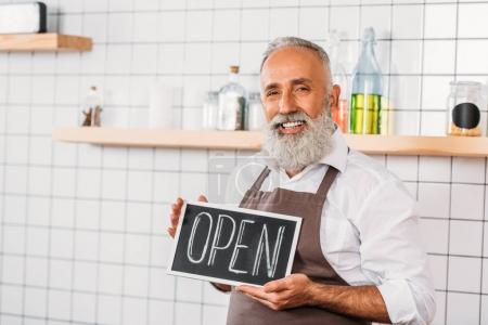 Photo for Portrait of smiling senior cafe worker in apron with open chalkboard - Royalty Free Image