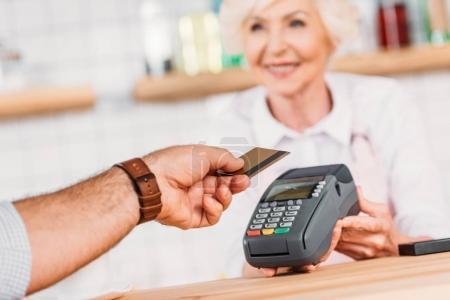 Photo pour Plan recadré de visiteur payant pour la commande avec carte de crédit dans le café - image libre de droit
