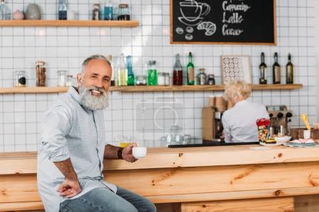 smiling senior man with cup of coffee