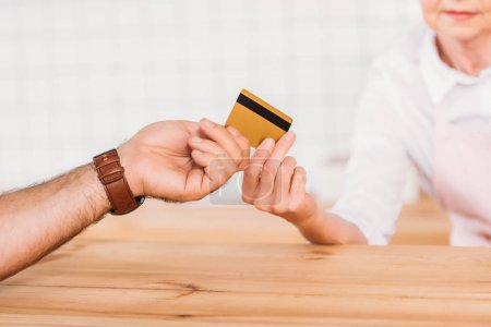 visitor giving credit card to cafe worker