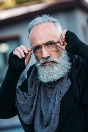 Foto de Senior hombre barbudo en ropa de moda y anteojos posando en la calle - Imagen libre de derechos