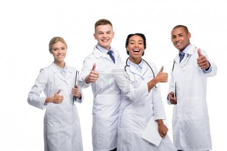 Photo for Multiethnic female and male doctors with thumbs up, isolated on white - Royalty Free Image
