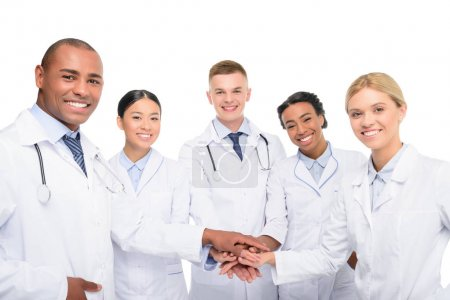 Photo for Multiethnic female and male doctors with hands together, isolated on white - Royalty Free Image