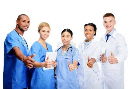 Photo pour Multiethniques chirurgiens et médecins avec les pouces vers le haut, isolé sur blanc - image libre de droit