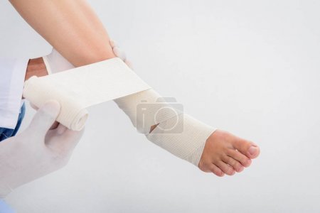 doctor puting bandage on leg