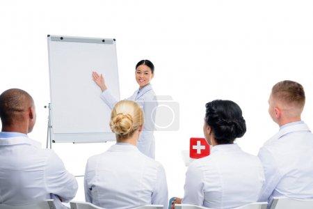 Photo pour Asiatique médecin présentant rouge trousse de premiers soins, isolé sur blanc - image libre de droit