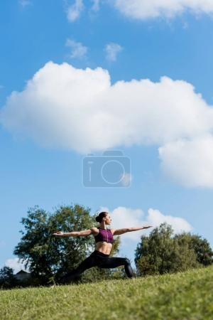 Photo for Young woman in warrior pose practicing yoga outdoors - Royalty Free Image