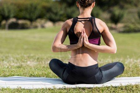 Photo pour Vue arrière de la jeune femme en pose de prière inversée pratiquant le yoga à l'extérieur sur tapis de yoga - image libre de droit