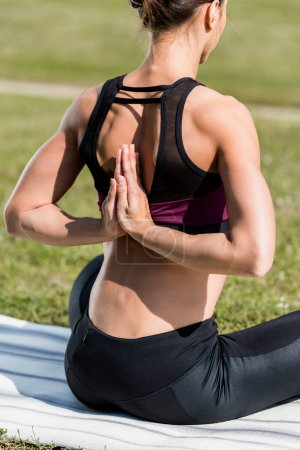 Photo for Woman in reverse prayer pose practicing yoga outdoors - Royalty Free Image