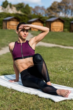 Photo for Young athletic woman sitting on yoga mat outdoors and looking away - Royalty Free Image
