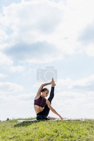 Photo for Young woman standing on one leg with other raised practicing yoga outdoors - Royalty Free Image