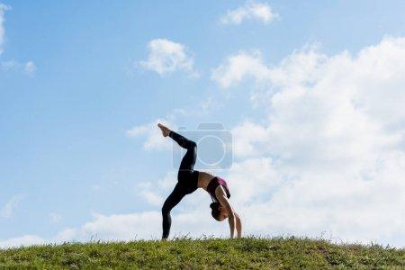 Photo pour Jeune femme en pose de pont pratiquant le yoga en plein air - image libre de droit