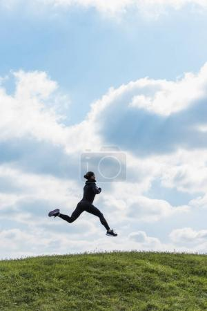 Sporty woman jumping on hill