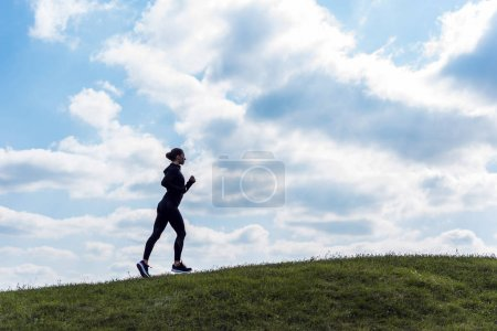 Sporty woman jogging on hill