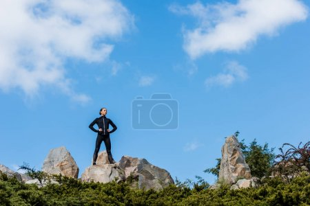 woman standing on rocks with arms akimbo
