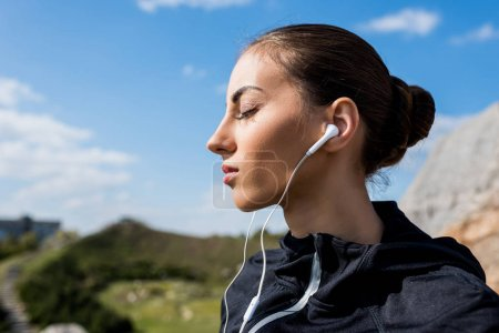 woman listening music outdoors