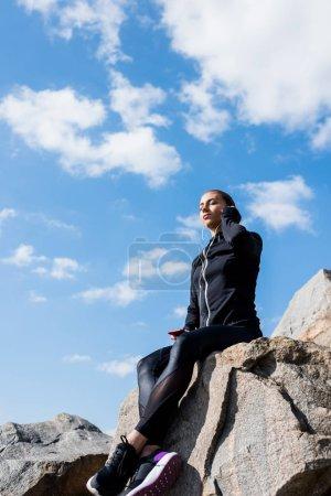 woman sitting on rocks and listening music