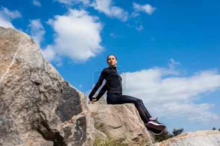 sportive woman sitting on rocks