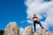 athletic woman standing on rocks